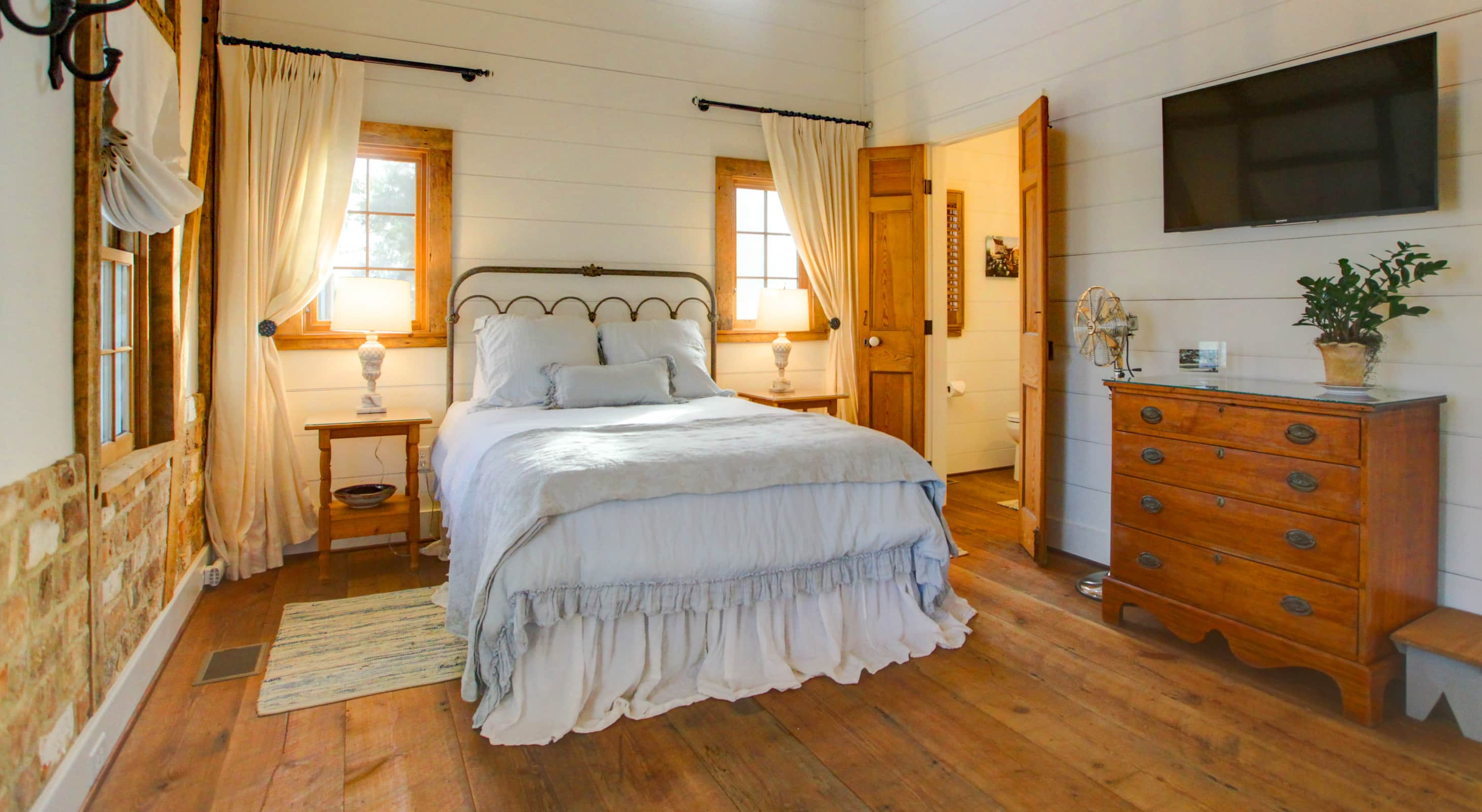 Queen bed in the Cottage with two end tables a flat screen TV and high ceilings